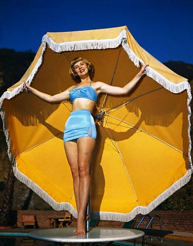 Dorothy Abbot Modeling Bathing Suit on Beach Table - Original Caption: Dorothy Abbot models a 1950 bathing suit at Franciscan pool in Hollywood.  Dorothy also appears in Paramount's Western film, <Copper Canyon.>  This photo has her head cocked to the left.