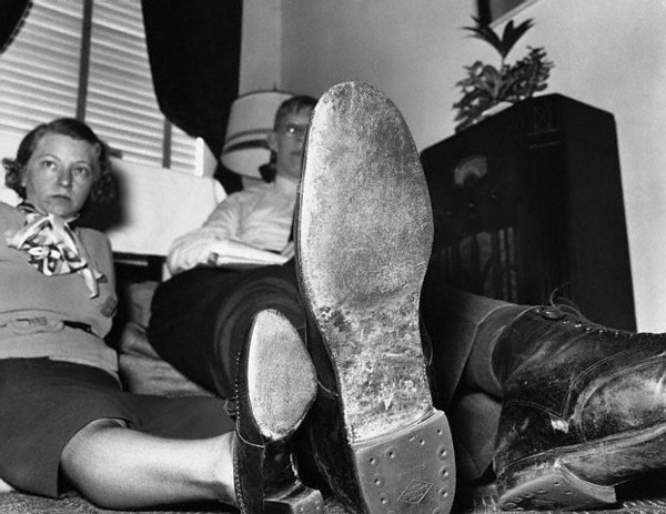 Robert Ludlow with Feet Next to Woman - 1937 --- Robert Wadlow is shown comparing his feet with Lora Petty as they sit on a couch. --- Image by © Bettmann/CORBIS