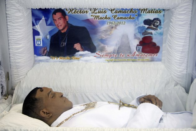 Puerto Rico Boxer Shot - The body of former boxing champion Hector ÒMachoÓ Camacho lies in an open casket during his funeral in San Juan, Puerto Rico, Tuesday Nov. 27, 2012.  Hundreds of people took pictures and filed past Camacho's open casket displayed inside a gymnasium. The boxer wore white, along with a large gold crucifix and a necklace spelling out his nickname, ÒMacho,Ó in capital letters. (AP Photo/Ricardo Arduengo)